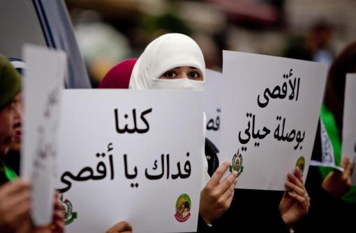 "Palestinian supporters of the Islamist movement Hamas, hold a placards with the slogan written in Arabic, ""we are all your defenders Al-Aqsa,"", and ""Al-Aqsa is the compass for my life"" during a protest against recent Israeli restrictions at the Al-Aqsa Mosque, in the West Bank City of Ramallah, Friday, Oct. 17, 2014. (AP Photo/Majdi Mohammed)"